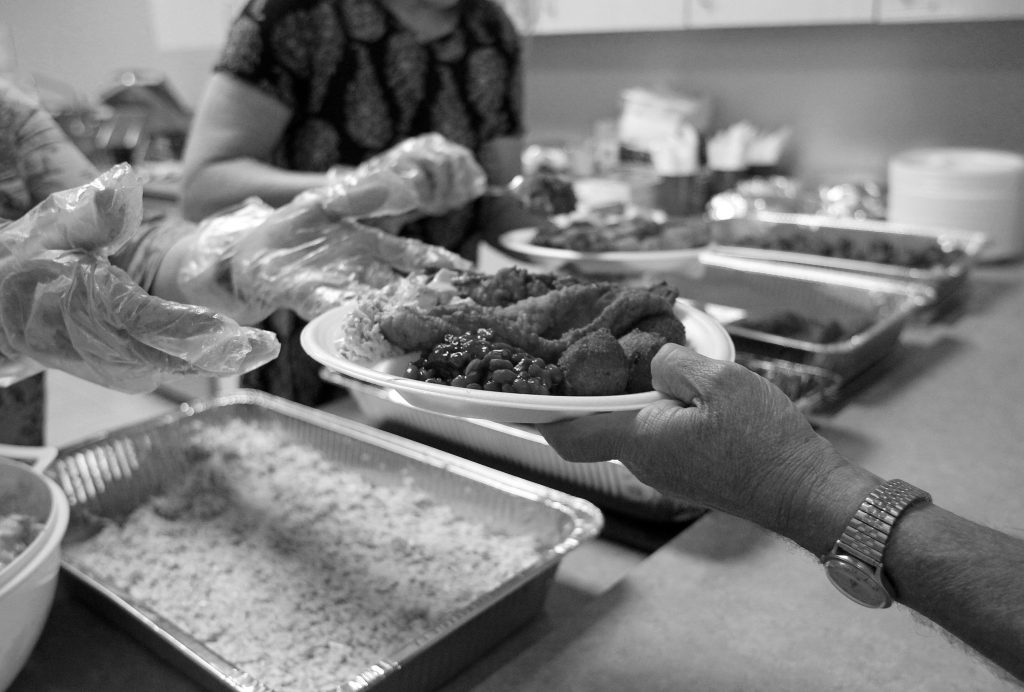 A black and white photo of a server's hands giving a resident a plate of food